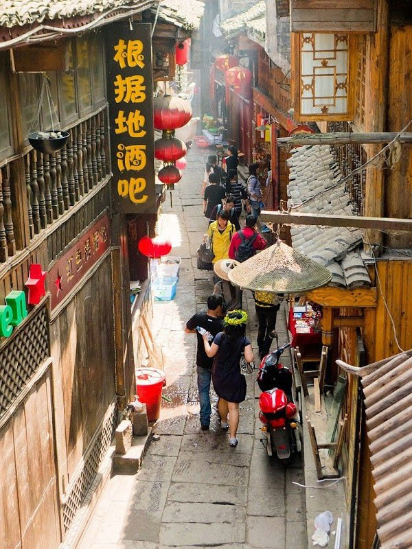 شخصان يسيران في شارع صيني ضيق