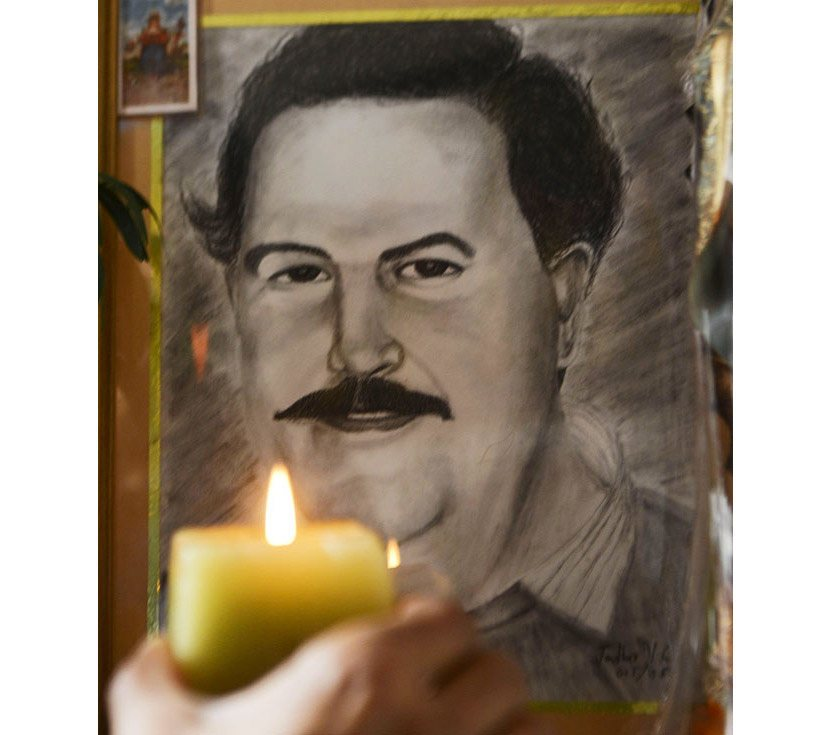 صورة بابلو إيسكوبار أمامها شمعة مضاءة