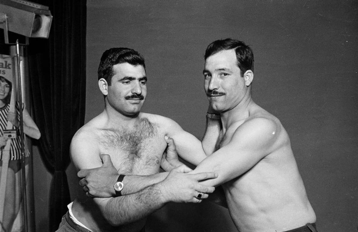 شابان يتموضعان لالتقاط صورة يقلدان فيها أبطال المصارعة الحرة في سنوات السبعينات.