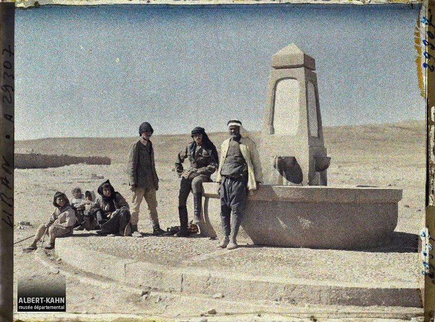 مجموعة من الأشخاص جالسون حول نافورة مياة بالقرب من قريةمجدل عنجر في لبنان سنة 1921.