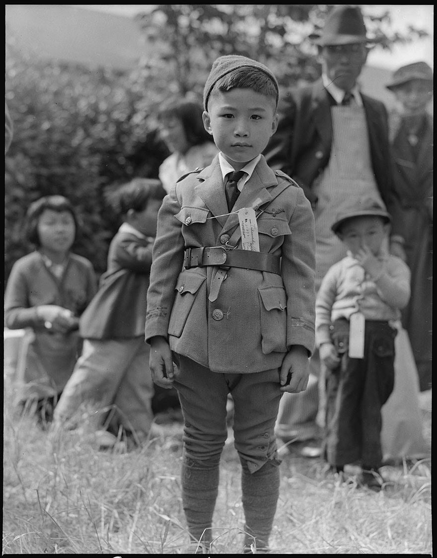 ورد في التعليق الكامل والأصلي لهذه الصورة: (سنترفيل)، (كاليفورنيا). ينتظر هذا الصغير حافلة الترحيل. تقرر لزوم بقاء المرحَّلين من المواطنين الأمريكيين من أصول يابانية في مراكز تابعة لسلطة الترحيل طوال مدة الحرب.