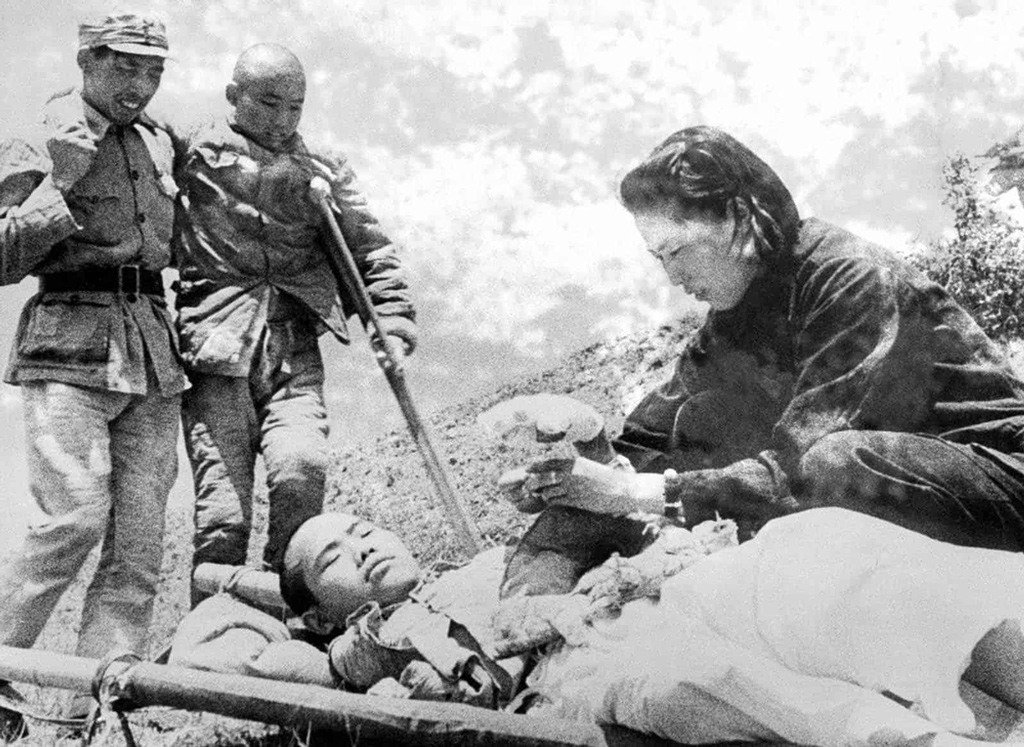 ممرضة وهي تلف ضمادة حول يد جندي صيني بينما يعرج جندي مصاب آخر متقدما من أجل تلقي العناية الطبية اللازمة، وذلك خلال المعارك التي دارت في جبهة نهر (سالوين)، في مقاطعة (يونان) في الصين في 22 يونيو سنة 1943.